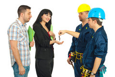 Workers giving keys to couple Royalty Free Stock Images