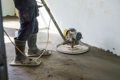 Grinding of concrete floor. Workers grind the concrete floor at the construction site royalty free stock photo