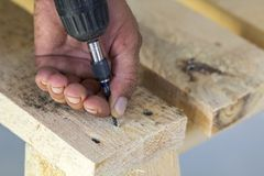 Workers hand with electric screwdriver screwing a screw into woo. Den board Royalty Free Stock Photos