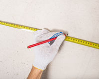 Workers hand measuring plaster wall Stock Image