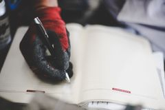 Workers hand writing in planer. Close up. Focus is on hand Stock Images