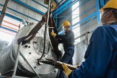 Workers handling equipment for lifting industrial boilers. Low-angle view of two workers handling equipment for lifting industrial steam boilers Stock Image