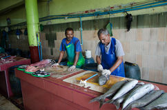 Workers handling fish on parts at fish market royalty free stock images