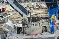 Workers handling massive cement pump tube and pouring fresh concrete on reinforced bars at new construction site royalty free stock photos