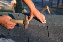 Workers hands installing bitumen roof shingles using hammer in nails stock photography