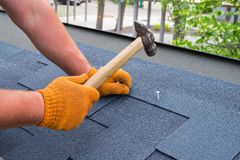 Workers hands installing bitumen roof shingles using hammer in nails stock photo