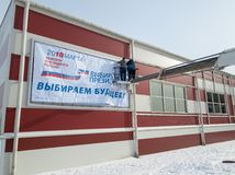 Workers hang an advertising poster with an appeal to come to the presidential election. Moscow - February 22, 2018: Workers hang an advertising poster with an Royalty Free Stock Images