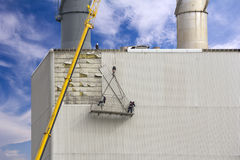 Workers hanging on the crane and repairing wall paneling on heat Royalty Free Stock Photos