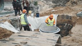 Workers in hard hats in sewer ditch talking to colleagues at building site stock footage