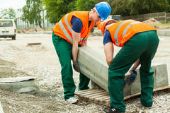 Workers heaving block of setts Royalty Free Stock Images
