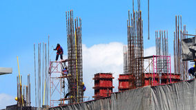 Workers on high building construction site. Stock Images