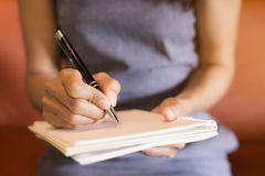 Workers hold a pen, note the work on the notebook. stock photo