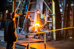 Workers hold the workpiece under the hammer. Heavy forgings Plant. workers hold red-hot billet under the hammer Stock Photo