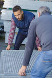 Workers holding sheet metal plates outside factory Stock Photos