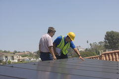 Workers Inspecting Solar Panels Stock Images