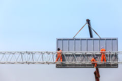 Workers install big steel billboard over highway Royalty Free Stock Images