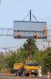 Workers install big steel billboard over highway Stock Image