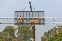 Workers install big steel billboard over highway Royalty Free Stock Photos
