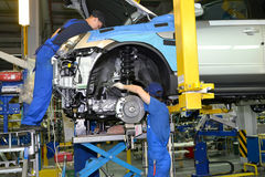 Workers install the engine on the car. Assembly conveyor of auto Royalty Free Stock Images