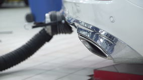 Workers install pipe to exhaust outlet of cars indoors stock video footage