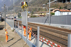 Workers during the installation of noise barriers on the railway. Capolago, Switzerland - 22 march 2012: Workers during the installation of noise barriers on the stock photography