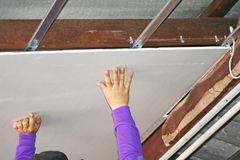 Workers are installing ceilings sheet. Close up Workers are installing ceilings sheet royalty free stock photo