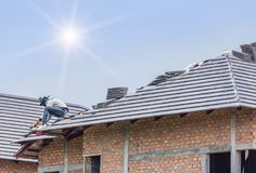 Workers installing concrete tiles on the roof while roofing house. In sunny day stock photos