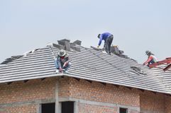 Workers installing concrete tiles on the roof while roofing house. In construction site royalty free stock photo