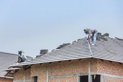 Workers installing concrete tiles on the roof. While roofing house royalty free stock photos