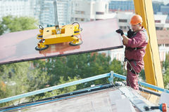 Workers installing glass window on building. Tho builders worker installing glass windows on facade of business building Stock Photography