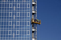 Workers installing glass window. On facade of modern business building Stock Photo