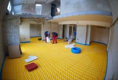 Workers installing underfloor heating system Stock Photos