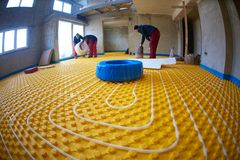 Workers installing underfloor heating system Stock Image