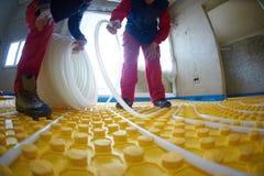 Workers installing underfloor heating system Royalty Free Stock Image