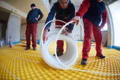 Workers installing underfloor heating system Royalty Free Stock Photography
