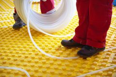 Workers installing underfloor heating system Stock Photo