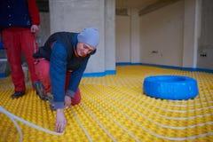 Workers installing underfloor heating system Royalty Free Stock Photos