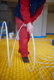 Workers installing underfloor heating system Royalty Free Stock Images