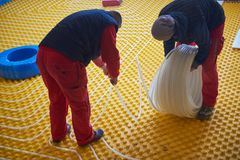 Workers installing underfloor heating system Stock Images