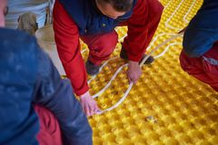 Workers installing underfloor heating system Royalty Free Stock Photo