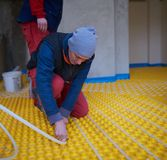 Workers installing underfloor heating system Royalty Free Stock Photo