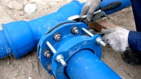Workers installing water supply pipeline system, close up