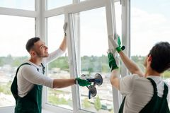 Workers installing a window. Two guys with uplifted mood are mounting a window section on hinges of the sash stock photo