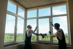 Workers are installing a window. Two men are holding and mounting a sash into the frame, using a vacuum lifter royalty free stock images