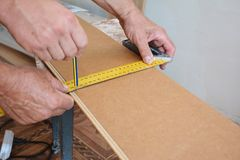 Workers installing wooden laminate flooring and measuring laminate board before cutting. Workers hands installing wooden laminate flooring and measuring Stock Image