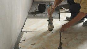 Workers installs ceramic tile in floor stock video