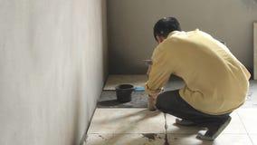Workers installs ceramic tile in floor stock video footage