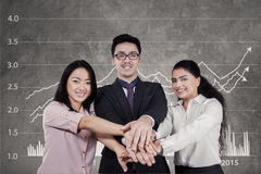 Workers joining hands with financial graph background Stock Images