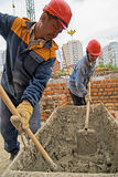 Workers knead solution for bricklayers. Tyumen, Russia - May 23, 2008: Construction of 18 floor brick residental house at intersection of streets of Gercena and Stock Photos