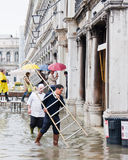 Workers with ladder. Venice Italy, 16 Nov 2011: Workers with ladder navigating a flooded St Marks Square, Venice Italy Stock Photo